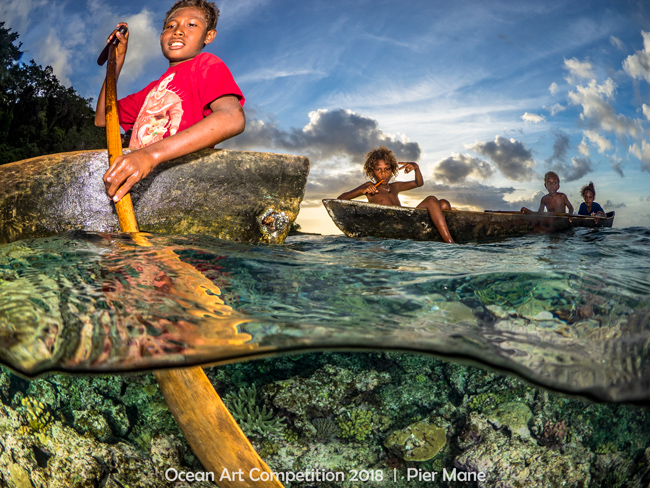 Solomon Island kids in canoes at sunset